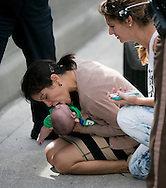 Pamela Rauseo, 37, performs CPR on her nephew, five-month-old Sebastian de la Cruz, after pulling her SUV over on the side of the road along the west bound lane on Florida state road 836 just east of 57th Avenue around 2:30pm on Thursday, February 20, 2014.  At right is Lucila Godoy who stopped her car to assist in the rescue.