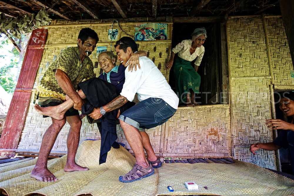 Two cousins carrying their 91 year old uncle from inside the hut onto the balcony..Wanokaka, Sumba, Indonesia 2011.