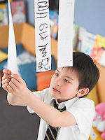 Elementary schoolboy learning to read from hanging paper strip in classroom elevated view