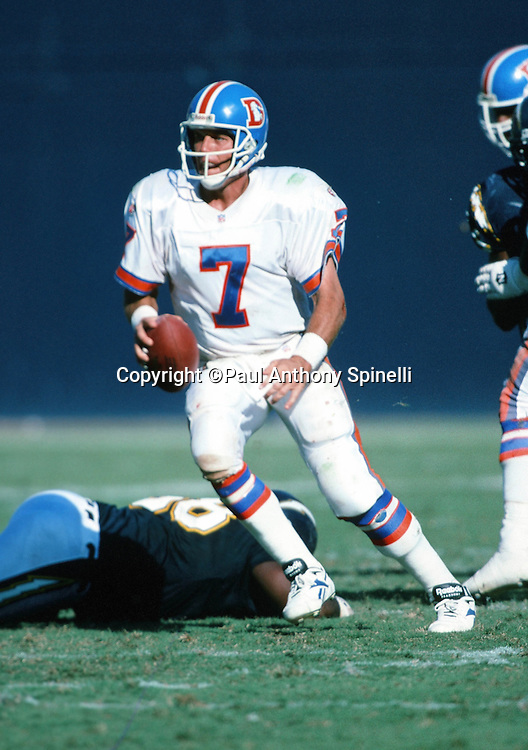 Denver Broncos quarterback John Elway (7) scrambles away from defensive pressure as he looks to pass during the NFL football game against the San Diego Chargers on Sept. 24, 1995 in San Diego. The Chargers won the game 17-6. (©Paul Anthony Spinelli)