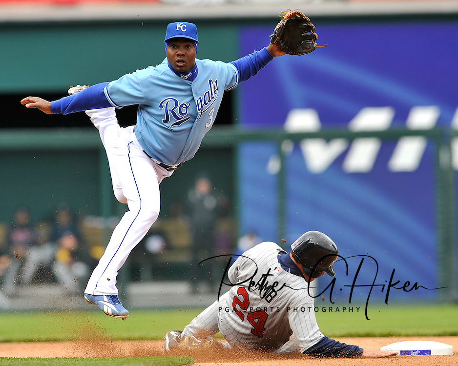 Second basemen Esteban German #3 of the Kansas City Royals leaps over Mike Lamb #24 of the Minnesota Twins after completing a throw to first for a double paly, during a Major League Baseball game at Kauffman Stadium in Kansas City, Missouri...