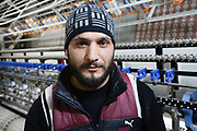 Gassem is from Duma, on the outskirts of Damascus. He came to Lebanon in 2011, just after the start of the uprising in Syria, and is now working in a Lebanese textile factory in the Bekaa Valley, thanks to a scheme supported by UK aid and the NGO Mercy Corps. <br /> <br /> &quot;I have been working here for 6 months. I like the work.<br /> <br /> &quot;I had difficulties finding a good job, until I came to work here.  I worked in different jobs, sometimes there was work, other times there wasn't.<br /> <br /> &quot;My situation is better now. Now I have been working constantly for 6 months, so I am managing. Of course I would like to go back to Syria. It is my country. Nowhere is better than one&rsquo;s homeland.<br /> <br /> &quot;But as long as I can work here, and it isn't safe to go back, then I'll stay here&quot;.<br /> <br /> UK aid is supporting Mercy Corps to create jobs in Lebanon, for Lebanese workers as well as Syrian refugees. The INTAJ (Improving Networks, Training and Jobs) programme is aimed at strengthening Lebanese communities by building stronger businesses and increasing employment.<br /> <br /> The Lebanese textile company that Gassem now works for received a grant last year to help it expand. The owner invested in a new electronic loom, helping increase his production capacity so that he needed to hire new employees. Over the past 12 months, he has taken on 6 Syrian staff and 4 Lebanese.<br /> <br /> Picture: Russell Watkins/DFID