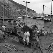 Miners working on the infamous mountain, Cerro Rico (rich mountain) overlooking the City of Potosi. Bolivia..Sitting at 4,090M (13,420 Feet) above sea level the small mining community of Potosi, Bolivia is one of the highest cities in the world by elevation and sits ?sky high? in the hills of the land locked nation. Overlooking the city is the infamous mountain, Cerro Rico (rich mountain), a mountain conceived to be made of silver ore. It was the major supplier of silver for the spanish empire and has been mined since 1546, according to records 45,000 tons of pure silver were mined from Cerro Rico between 1556 and 1783, 9000 tons of which went to the Spanish Monarchy. The mountain produced fabulous wealth and became one of the largest and wealthiest cities in Latin America. The Extraordinary riches of Potosi were featured in Maguel de Cervantes famous novel Don Quixote. One theory holds that the mint mark of Potosi, the letters PTSI superimposed on one another is the origin of the dollar sign. Today mainly zinc, lead, tin and small quantities of silver are extracted from the mine by over 100 co-operatives and private mining companies who still mine the mountain in poor working conditions, children are still used in the mines and the lack of protective equipment and constant inhalation of dust means miners have a short life expectancy with many contracting silicosis and dying around 40 years of age. UNESCO designated the historic city a World Heritage site in 1987. Most of Potosí's colonial churches have been restored, and tourism has increased. Potosi, Bolivia. 16th September 2011. Photo Tim Clayton
