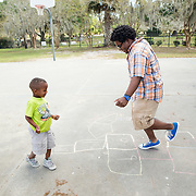 Ke'Sean Davis, 5-years-old plays hopscotch with University of Florida student Dashari Kearse, 20 at the Woodland Park Boys and Girls Club of Alachua County on Wednesday.  Kearse visits the boys and girls club twice monthly to spend time with the children as a member of the service group Progressive Black Men, Inc. at the University of Florida. [Photo Willie J. Allen Jr.]