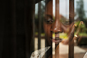 """Goma, DRC -   2014-08-28 -  Rehema Jeanne Bonane, a counsellor at HEAL Africa for women who have been victims of sexual violence looks out the window of her office in Goma, DRC on August 28, 2014. """"The counselling work is heavy and hard. Currently we are seeing very violent cases. In the past it was just a grown man raping a grown woman but now it's very violent and even against children,"""" says Rehema, who was herself raped by a Rwandan refugee in 1999. She became pregnant and gave birth to twins. Rehema was consequently expelled from school and ostracized by her parents. """"They refused to believe sexual violence existed,"""" says Rehema, who began working at HEAL Africa in 2002 after hearing an appeal from co-founder Lyn Lusi at a church. """"We are thankful for the support of CBM, the ladies here are very grateful. We'll always keep CBM in our minds. Please tell our brothers and sisters: never stop thinking about us, we are also your brothers and sisters."""" Today, she is married and one of the twins (one died as an infant) in secondary school at the top of his class.  Photo by Daniel Hayduk"""