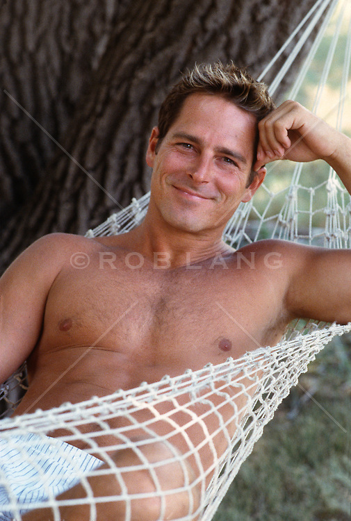 Good looking shirtless man in a tree hammock