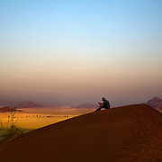 A tourist sits atop Elim dune as he watches the moon rise as the sun sets over Sossusvlei. Namibia boasts the world?s oldest and largest sand dunes, extending for 400 miles along the coast and more than 80 miles inland. July 17, 2008. Photo by Evelyn Hockstein for The New York Times.