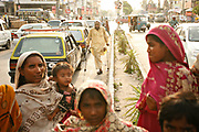 Nasim Khokhar, 35, left, holds her youngest daughter Gori, as she other family members, including Abdul Rauf, on crutches, work the traffic stopped at a busy intersection in Rawalpindi, Pakistan, for handouts.  All of the women in Khokar's family beg on the streets, while the men typically work or go to school, unless their disabled, like Rauf, who can bring in more Rupees begging than working.