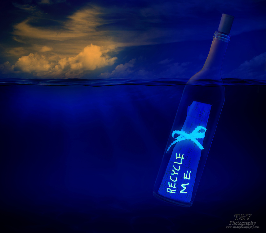 A recycle me message in a bottle floats in the ocean at dusk.Black light