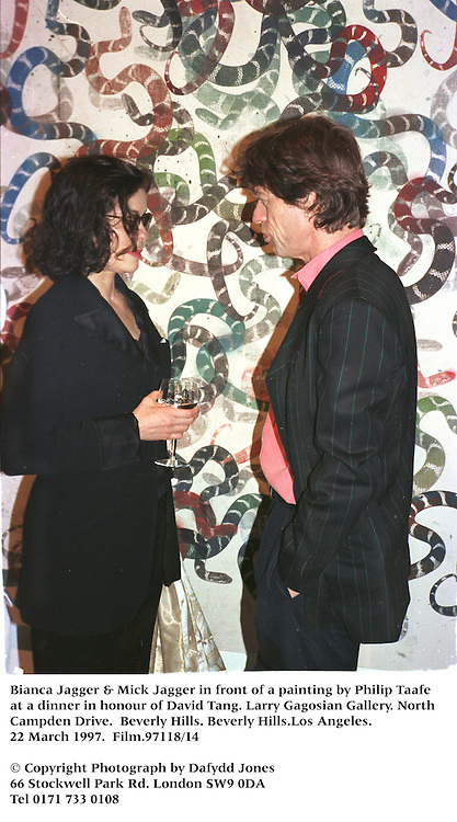 Bianca Jagger & Mick Jagger in front of a painting by Philip Taafe at a dinner in honour of David Tang. Larry Gagosian Gallery. North Cam[pden Drive. Beverly Hills. Beverly Hills.Los Angeles. 22 March 1997. Film.97118/14<br />© Copyright Photograph by Dafydd Jones<br />66 Stockwell Park Rd. London SW9 0DA<br />Tel 0171 733 0108