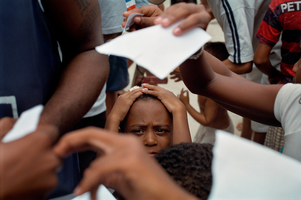 Frustrated child caught in the middle of a crowd of fans wanting to get an autograph from the Brazillian rapper MV Bill who is visiting the Vigario Geral favela. He released a controversial song about gun violence recently. Rio de Janerio, Brazil. 2001