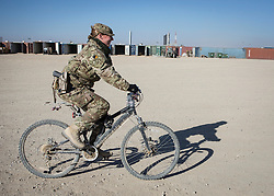 "24/12/2013.  Lance Corporal Michelle Mackay (37) prepares for Christmas Day in Camp Bastion, Afghanistan by decorating her mountain bike with tinsel and baubles.  This will be her first Christmas away from home and as an Army Reservist, her first tour in Afghanistan.  ""Back in the UK I'm a Police Community Support Officer (PCSO) and I patrol on my bike, so this is just the same, only in Afghanistan!"".  Photo credit: Alison Baskerville/LNP"