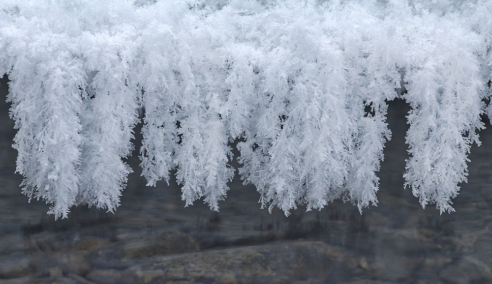 Hoar frost hanging from ice along stream in Southcentral Alaska. Afternoon. Winter.