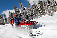 Couple driving snowmobile through snow
