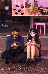 London, January 01 2018. A couple sit on the pavement in Soho looking at their phones as revellers in London's West End enjoy New Year's Eve. © SWNS