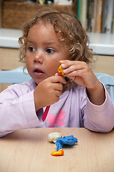 Portrait of a young girl playing with plasticine,
