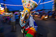 27 JUNE 2014 - DAN SAI, LOEI, THAILAND: A ghost dances in downtown Dan Sai during the Phi Ta Khon. Phi Ta Khon (also spelled Pee Ta Khon) is the Ghost Festival. Over three days, the town's residents invite protection from Phra U-pakut, the spirit that lives in the Mun River, which runs through Dan Sai. People in the town and surrounding villages wear costumes made of patchwork and ornate masks and are thought be ghosts who were awoken from the dead when Vessantra Jataka (one of the Buddhas) came out of the forest.    PHOTO BY JACK KURTZ