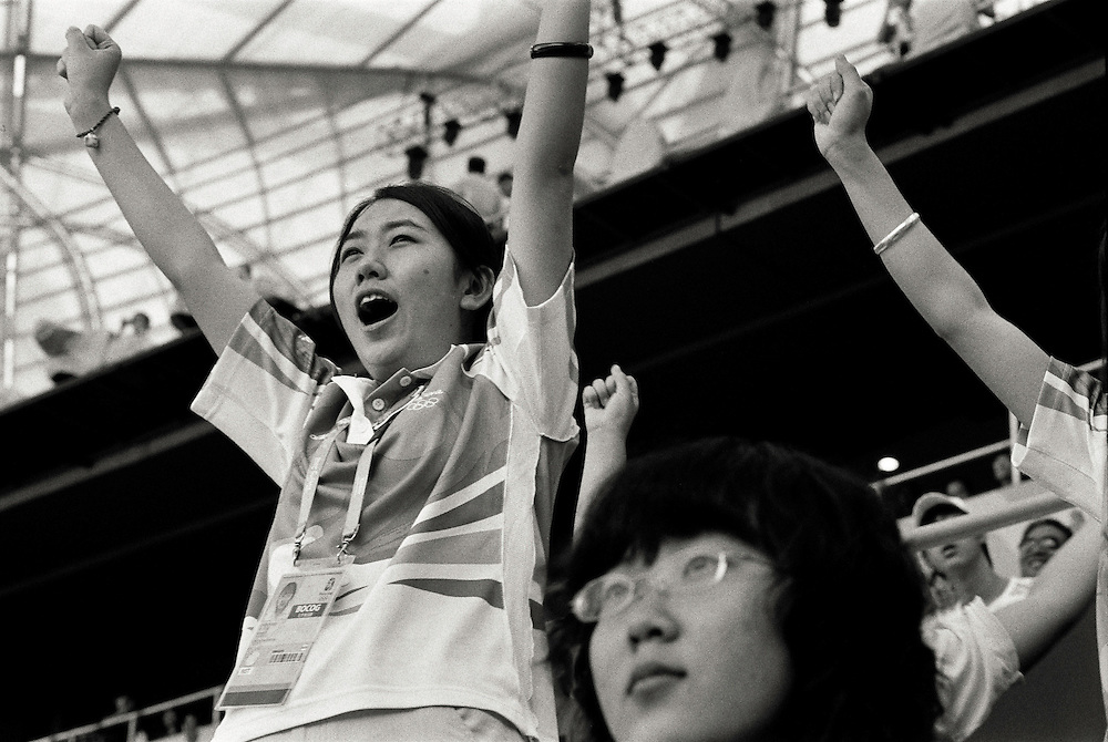 Olympic Games Athletics Day 11<br /> A young chinese volunteer supporting athletes in the National Olympic Stadium<br /> A young chinese volunteer is supporting chinese athletes with spectators while looking at the competitions in the Olympic stadium, morning of the august 19 2008 High Resolution available