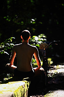 man in a yoga lotus position in the rain forest of tijuca in rio de janeiro brazil