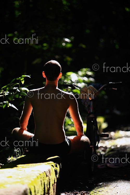 man in a yoga lotus position in the rain forest of tijuca in rio de janeiro brazil