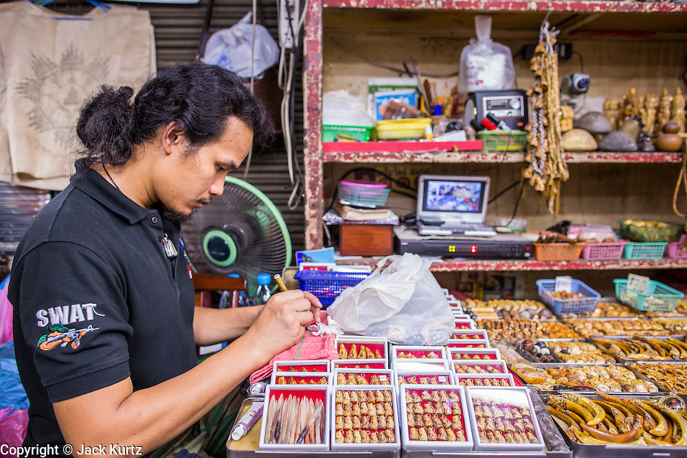 05 OCTOBER 2012 - BANGKOK, THAILAND:  A craftsman works on an amulet in his shop in the amulet market in Bangkok. Hundreds of vendors sell amulet and Buddhist religious paraphernalia to people in the area north of the Grand Palace near Wat Maharat in Bangkok.        PHOTO BY JACK KURTZ