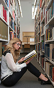 A student, a young woman with long hair and glasses, sits by herself between book shelves at a UK University.