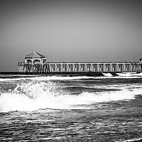 Black and white picture of Huntington Beach Pier. Huntington Beach Pier is a registered historic place and has a Ruby's Restaurant at the end. Huntington Beach is a seaside beach city along the Pacific Ocean in Orange County Southern California and is also known as Surf City USA.