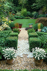 General view of the garden. Gravel and brick path leading through low clipped hedging to lawn beyond. Design: Anthony Goff