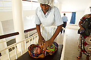 A nurse pushes a craddle with a sleeping newborn baby through hallways at the Princess Christian Maternity Hospital in Freetown, Sierra Leone on Monday April 26, 2010.