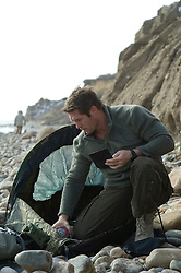 man setting up a tent on the beach in Montauk
