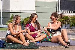 © Licensed to London News Pictures. 07/08/2020. London, UK. Friends enjoy a cooling drink in the sunshine next to the River Thames at Richmond in South West London as temperatures are expected to reach to 35c today. Thousands of sun seekers have flocked to parks, rivers and the south coast as temperatures soar with beaches and roads becoming jammed with holidaymakers. The heat is set to continue for the rest of the week with temperatures expected in the high 20s. Photo credit: Alex Lentati/LNP
