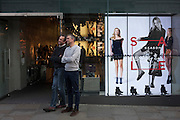 Two men wait patiently outside a Covent Garden womenswear shop in central London.