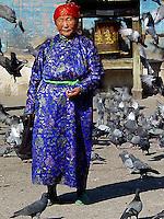 Traditionally dressed Mongolian woman feeding the pidgeons outside Ganden Monastery in Ulaan Bataar.
