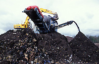 green waste being screened for unsuitable material after composting