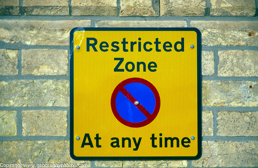 A3ABJ9 Restricted zone yellow rectangular no parking street sign fixed on brick wall