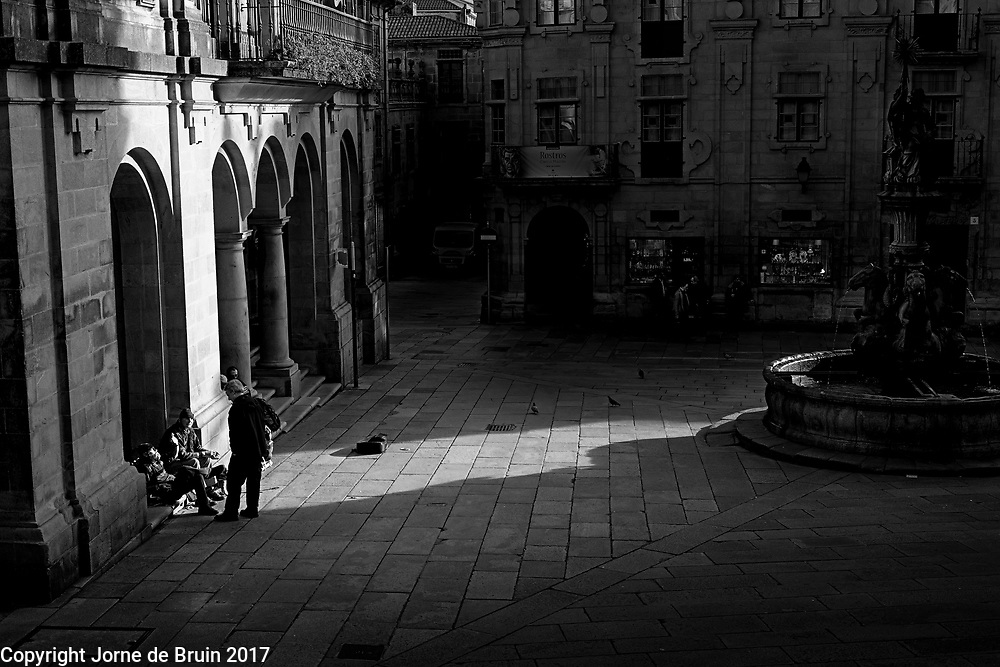 Light shines on streeet musicians in one of the old squares of Santiago de Compestela, Spain.