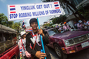 01 FEBRUARY 2014 - BANGKOK, THAILAND: An anti-government protestor carrying a sign calling for Thai Prime Minister Yingluck Shinawatra to step down. (The protestor misspelled Yingluck's name.) The anti-government protest movement, led by the People's Democratic Reform Committee (PDRC) organized a march through the Chinatown district of Bangkok Saturday and disrupted the city's famous Chinese New Year festival. Some streets were blocked and protest leader Suthep Thaugsuban walked through the neighborhood collecting money. The march was in advance of massive protests the PDRC has promised for Sunday, Feb. 2 in an effort to block Thais from voting in the national election.     PHOTO BY JACK KURTZ