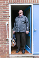 Older man standing at his front door about to go out shopping,
