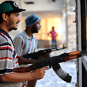 Rebel fighters takes guard in Jewel Hotel's main lobby in central  Zawiyah.