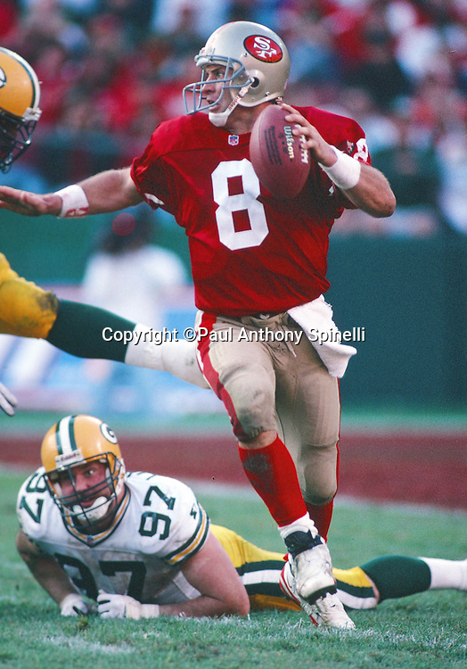 San Francisco 49ers quarterback Steve Young (8) runs away from a tackle attempt by Green Bay Packers defensive end Matt LaBounty (97) during the NFL NFC Divisional Playoff football game against the Green Bay Packers on Jan. 6, 1996 in San Francisco. The Packers won the game 27-17. (©Paul Anthony Spinelli)