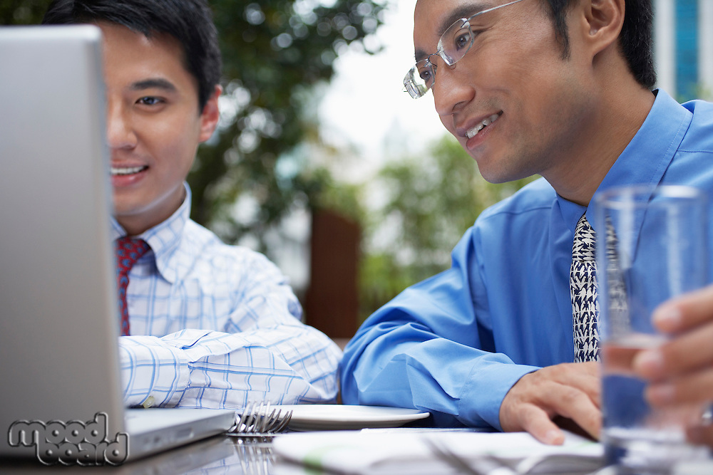 Two business man using laptop sitting in outdoor cafe close up