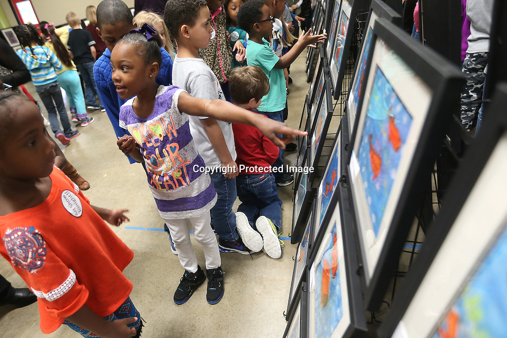 Lauren Wood | Buy at photos.djournal.com<br /> First grader Saniyah Middlebrooks points to her koi fish painting as she and other students at Thomas Street Elementary School walk through the gym looking at the art of all the students Monday afternoon. Art teacher Michelle Guyton said the students created Japanese-style art to introduce them to Japanese culture, leading up to the school's cherry blossom festival.