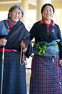Two women dressed in traditional Tibetan costume Chupa with mala beads in hand photographed at Dalai Lama Temple in Dharamsala of McLeod Ganj, India