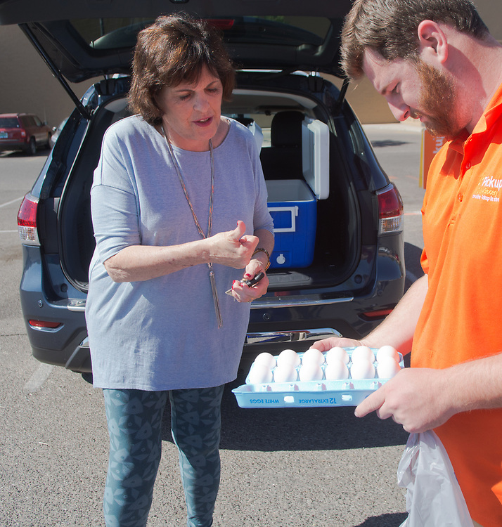 mkb063017c/living/Marla Brose --  Patricia Di Vasto gives a thumbs up as Walmart's Logan Huntington, an online grocery associate, shows her a carton of eggs, while loading Di Vasto's online ordered groceries into her car, Friday, June 30, 2017, in Rio Rancho, N.M. (Marla Brose/Albuquerque Journal)
