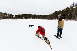 Two men and a dog walk on Round Pond in winter. Barrington, New Hampshire.