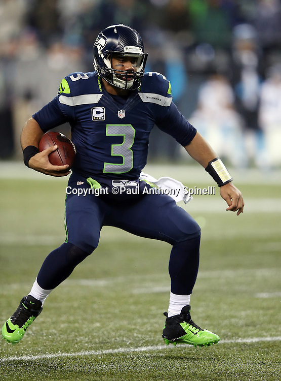 Seattle Seahawks quarterback Russell Wilson (3) runs the ball on a third quarter keeper for a short gain during the NFL week 19 NFC Divisional Playoff football game against the Carolina Panthers on Saturday, Jan. 10, 2015 in Seattle. The Seahawks won the game 31-17. ©Paul Anthony Spinelli