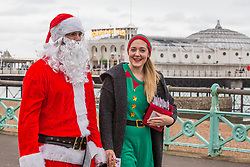 © Licensed to London News Pictures. 17/12/2017. Brighton, UK. Members of the public dressed as Santa Clause and an Elf on the Brighton and Hove promenade. Photo credit: Hugo Michiels/LNP