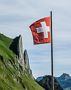 Swiss flag. The flag of Switzerland is red with a white equilateral cross in the center. It is one of only two square sovereign-state flags (the other being the flag of Vatican City). In contrast, the civil and state ensign of Switzerland, used by Swiss vessels and non-governmental bodies, is rectangular with the more common proportions of 3:2. Use of the white cross as a military ensign (attached to the cantonal flags in the form of strips of linen) has been used in the Old Swiss Confederacy since the 1300s, but the modern design was first used in 1800 during Napoleon's Hundred Days, and was introduced as official national flag in 1889. Below Bötzel pass, Widderalp comforts hikers with a homey restaurant and dormitory style (Matratzenlager) lodging, in the Alpstein limestone range, Appenzell Alps, Switzerland, Europe.