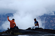 La Gran Sabana, Venezuela, 14-04-2011. Cargadores indigenas descansan al borde del Roraima tepuy en La Gran Sabana.  Al fondo el Kukenam tepuy. Localizada al sur de Venezuela en el macizo Guayanés en la parte sureste del Estado Bolívar hasta la frontera con Brasil. En ella conviven diversos grupos indígenas, entre ellos la etnia Pemón. La Gran Sabana forma parte de uno de los Parques Nacionales más extensos de Venezuela, el Parque Nacional Canaima. La Gran Sabana, 14 Abril  de 2011. .(Ramon Lepage / Orinoquiaphoto/ LatinContent/Getty Images)..Trail to Kukenam and Roraima tepui. Tepuis are large mesas that rise out of dense jungle in southeast Venezuela and adjacent Brazil and Guyana. Over 100 of these plateaus rise above the verdant landscape of this region, which is known in Venezuela as the Gran Sabana and also the Guyana Highlands. Tepuis are comprised of Precambrian sandstone, and are some of the oldest exposed rock formations in the world. Monte Roraima is one of the best known of the tepuis and has a labyrinth of rock forms and endemic plants on its summit..