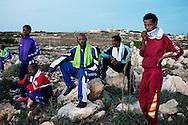 Lampedusa, Italia - 7 ottobre 2013. Immigrati ritratti su una collina all'esterno del CPT (Centro Permanenza Temporanea) di Lampedusa.<br /> Ph. Roberto Salomone Ag. Controluce<br /> ITALY - Immigrants are seen outside the temporary accomodation center (CPT) of the italian island of Lampedusa on October 7, 2013.